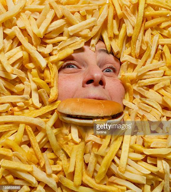 drowning in junk food - excess stock photos and pictures