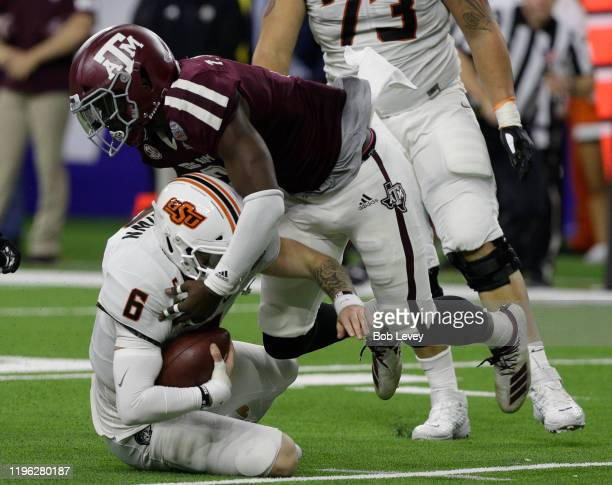 Dru Brown of the Oklahoma State Cowboys is sacked by Tyree Johnson of the Texas A&M Aggies during the second quarter during the Academy Sports +...