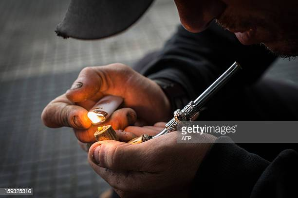 A drug addict lights an improvised pipe in Crackolandia a place where drug addicts gather to smoke crack in downtown Sao Paulo Brazil on January 11...