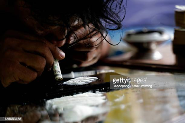 drug addict man sniffing cocaine lines on smart phone with rolled banknote. drug abuse concept. - dose foto e immagini stock