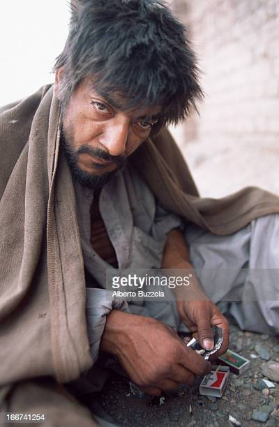 A drug addict prepares his daily heroin dose to be inhaled with the help of a straw and a little silver papermade tray