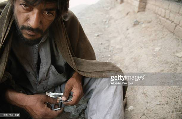 A drug addict prepares his daily heroin dose to be inhaled with the help of a straw and a silver papermade tray
