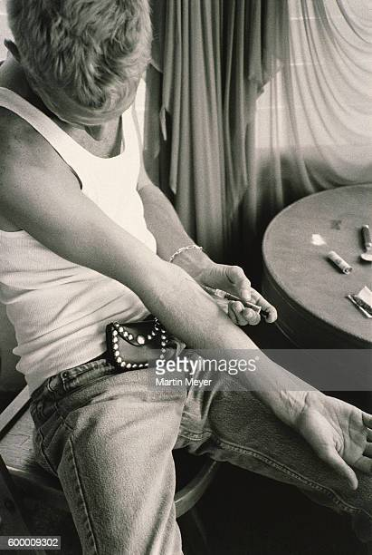 drug addict putting syringe - heroin addict arm stock photos and pictures