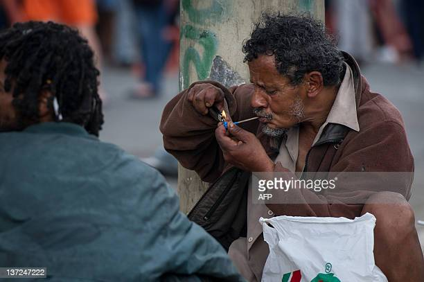 A drug addict smokes crack cocaine in a street in Cracolandia in downtown Sao Paulo Brazil on January 14 2012 AFP PHOTO / Yasuyoshi Chiba