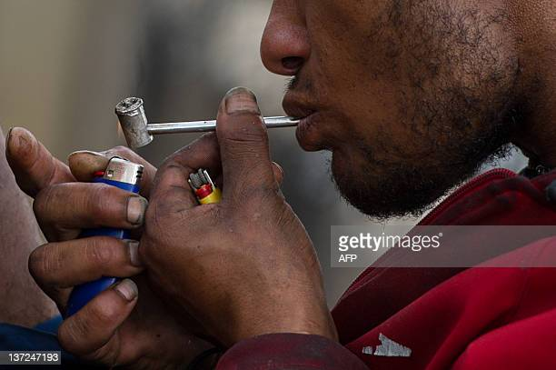 A drug addict smokes crack on the street in an area called Cracolandia in downtown Sao Paulo Brazil on January 14 2012 AFP PHOTO / Yasuyoshi Chiba