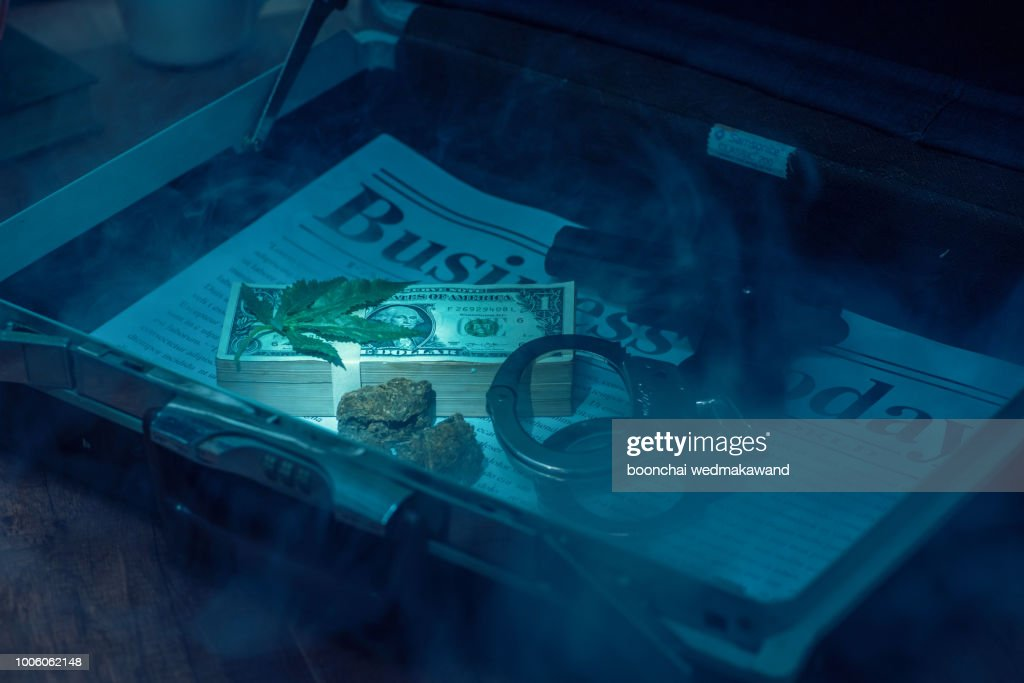 Drug bust arrest with handcuffs, cash, and fake sample evidence. : Stock Photo