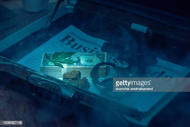 Drug bust arrest with handcuffs, cash, and fake sample evidence.