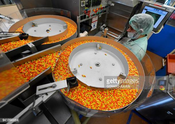 Drug capsules are seen on the production line at the plant of French multinational pharmaceutical company 'Pierre Fabre' in Gien on March 21 2018 The...