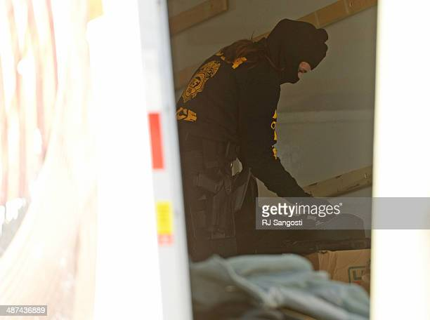 Drug Enforcement Agency agent loads items into a UHaul moving during a raid at VIP Cannabis located at 2949 W Alameda Ave April 30 2014 The marijuana...