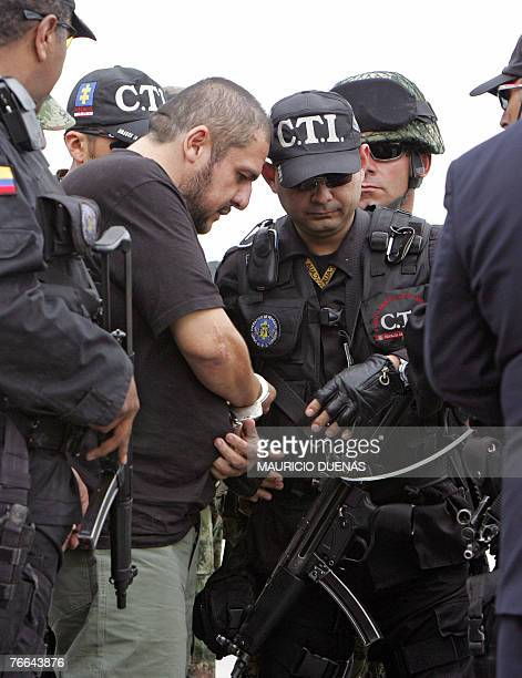 Drug lord Diego Leon Montoya Sanchez aka Don Diego is handcuffed by a Colombian soldier in Bogota after being flown from where he was captured 10...