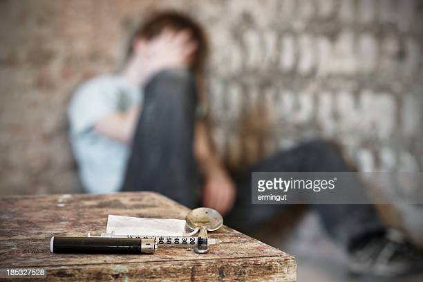 drug paraphernalia with blurred addict behind - enslaved stock pictures, royalty-free photos & images