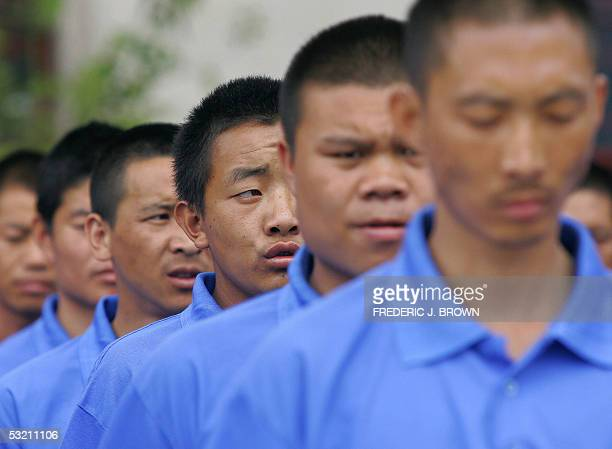 Drug rehab patients practice marching in a compound at the Kunming Municipal Compulsory Rehabilitation Center 08 July 2005 in Kunming in southwest...