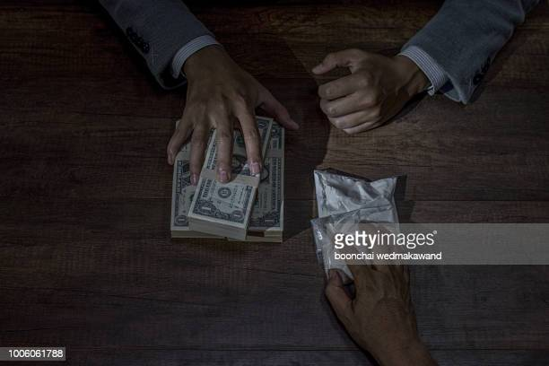 drug trafficker holding a lot of cash on hand and use gun pushing drugs to the customer in the drug dealing, concept about the drug problem - heroin stock-fotos und bilder