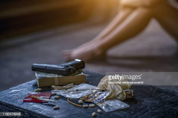 drug trafficker holding a lot of cash on hand and use gun pushing drugs to the customer in the drug dealing, concept about the drug problem - crime or recreational drug or prison or legal trial bildbanksfoton och bilder