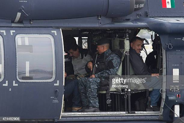 """Drug trafficker Joaquin """"El Chapo"""" Guzman, in white, is seated in a helicopter with Mexican security forces in Mexico city, Mexico, on Saturday, Feb...."""