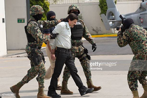 Drug trafficker Joaquin El Chapo Guzman is escorted to a helicopter by Mexican security forces at Mexico's International Airport in Mexico city...
