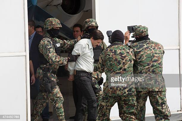 """Drug trafficker Joaquin """"El Chapo"""" Guzman is escorted to a helicopter by Mexican security forces at Mexico's International Airport in Mexico city,..."""