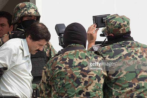 Drug trafficker Joaquin 'El Chapo' Guzman is escorted to a helicopter by Mexican security forces at Mexico's International Airport in Mexico city...