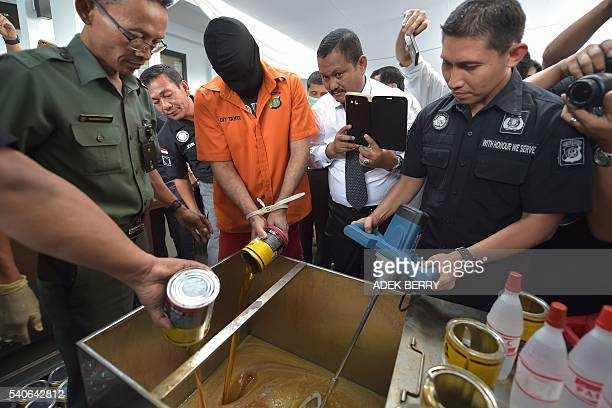 A drug trafficking suspect and Indonesian police officials pour out cans of liquid amphetamine to be destroyed during a presentation to the media as...