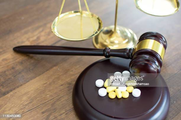 drugs and law. judge gavel and colorful pills on a wooden desk, dark background, closeup view - medical malpractice stock photos and pictures
