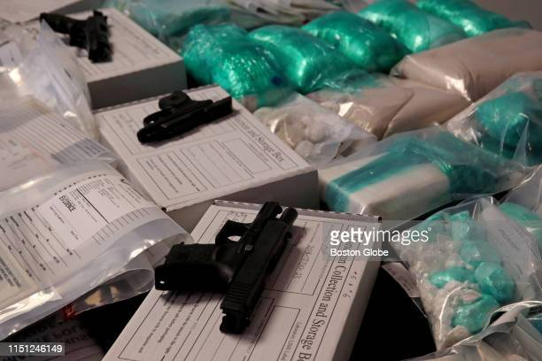 Drugs and weapons are displayed as evidence during a press conference at the Attorney General's office in Boston on June 20, 2019. Massachusetts...