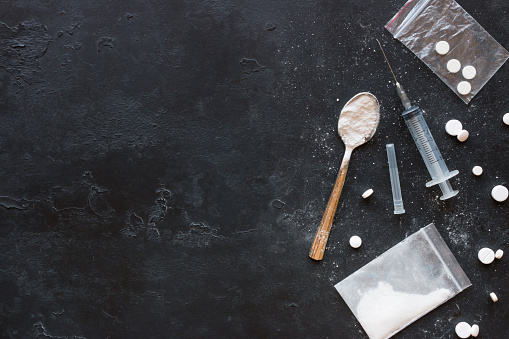 Drugs in the form of powder and tablets, a spoon and a syringe on a black background mockup 691978916
