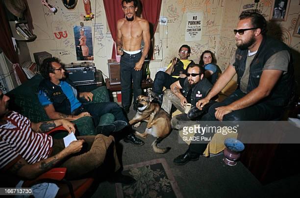 Drugs Lsd Aux EtatsUnis dans une pièce des hommes tatoués et une femme assis dans des canapé au milieu d'eux un homme debout torse nu