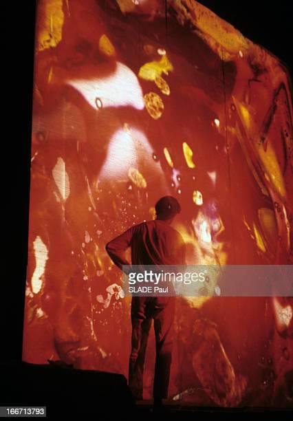 Drugs Lsd Aux EtatsUnis un homme debout devant un écran recevant une projection de lumière aux motifs psychédéliques