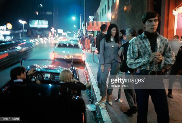 Drugs Lsd Aux EtatsUnis une rue éclairée par des enseignes lumineuses avec des passants et des automobilistes avec des effets spéciaux de flou