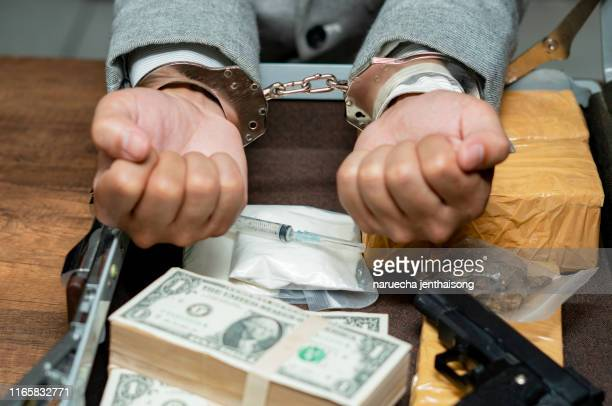 drugs money and gun on wooden table in concept about danger and threat of the drug,the drug dealer was arrested in handcuffs. - cocaine stock pictures, royalty-free photos & images