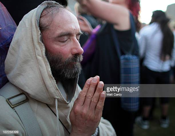 A druid meditates during a Solstice sunset service as people gather in the megalithic monument of Stonehenge on June 20 2010 on the edge of Salisbury...