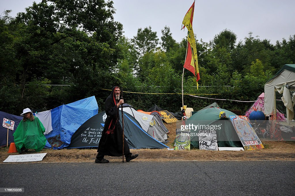 A druid walks past tents erected by protesters at the gates of the drill site operated & A druid walks past tents erected by protesters at the gates of the ...