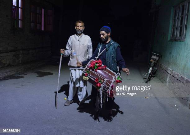 Drum beater along his colleague beating a drum walk through the streets of the city to wake up the Muslims to eat their meals before dawn on the 10th...