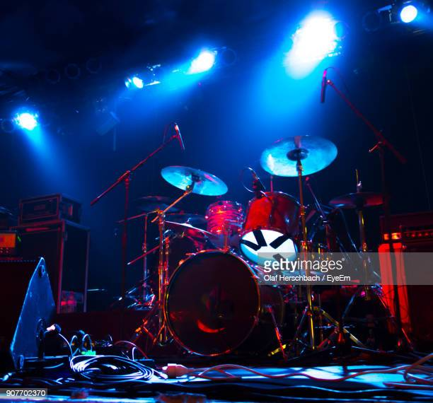 drum kit on illuminated stage - drum kit stock photos and pictures