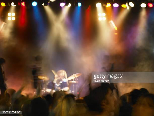 Drum kit on stage under strobe lights, audience in foreground