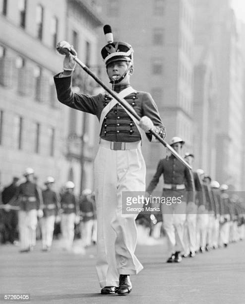Drum major leading parade in old-fashioned uniforms, (B&W)