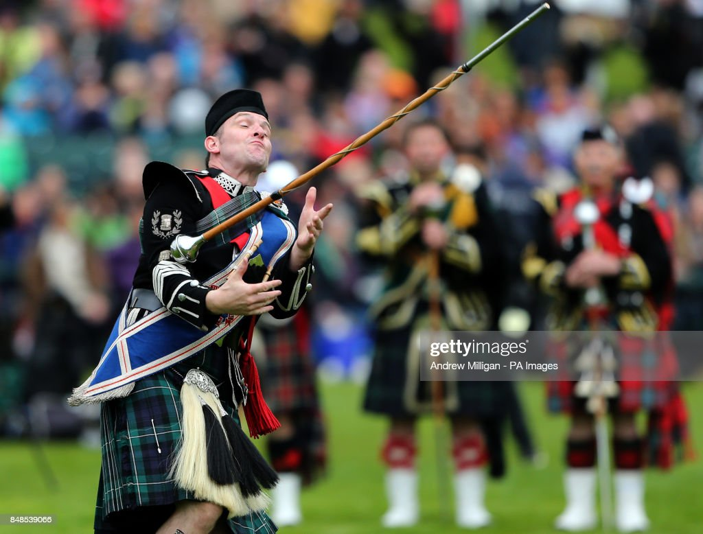 Drum Major Roland Stuart attempts to catch a piper's mace during