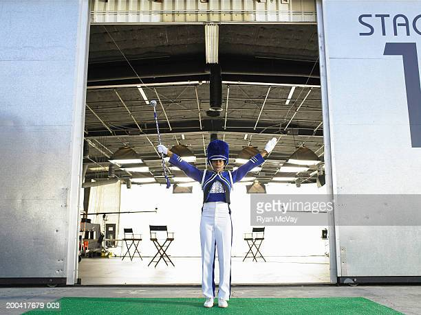 Drum majorette blowing whistle in front of stage door, arms raised