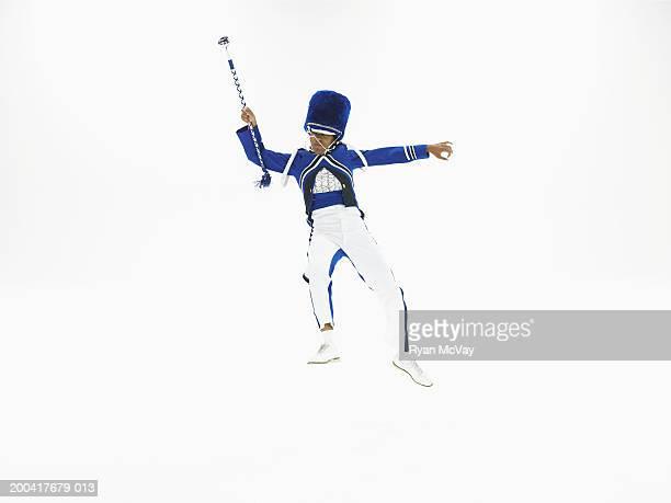 Drum majorette holding baton, dancing
