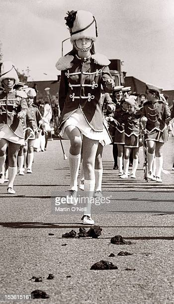 A Drum Majorette looks like she's about to encounter a rather messy problem as she follows behind some horses at a parade in Runcorn Cheshire circa...