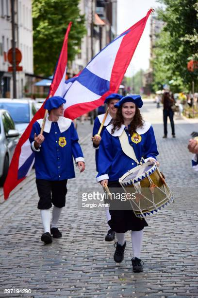 Drummer and two flag bearers in medieval costumes in Antwerp