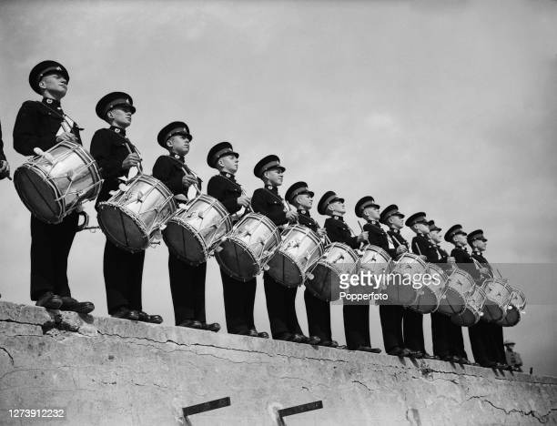 Drummer Boy cadets of the Royal Marines Band Service of the Royal Navy play their drums on top of a concrete wall at a Marines base in England during...