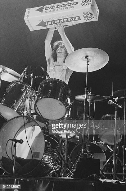 Drummer Don Powell of English rock group Slade holding up a giant model pack of chewing gum at one of the band's two nights at the New Victoria...