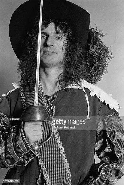 Drummer Don Powell of English rock group Slade posing in a cavalier costume and holding a sword London 1974