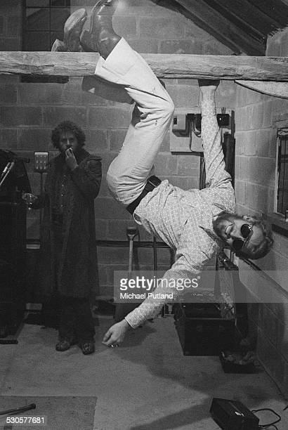 Drummer Ginger Baker, of English rock group the Baker Gurvitz Army, hanging from a roof beam, December 1974. In the background is guitarist and...