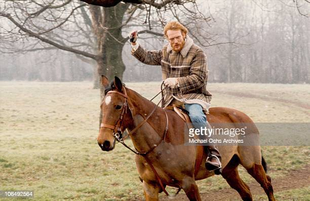 Drummer Ginger Baker poses for a photo on his horse circa 1975