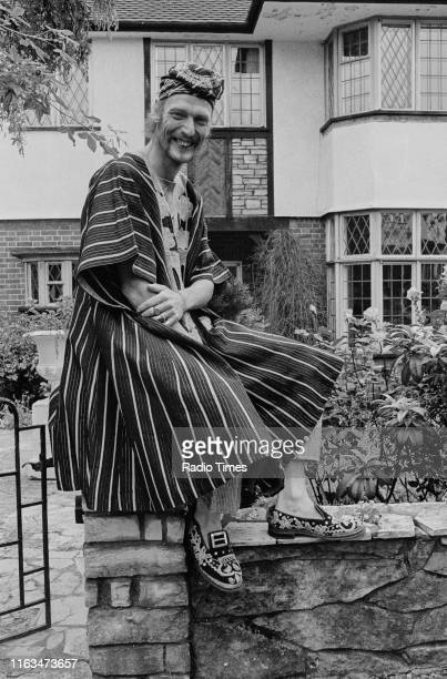 Drummer Ginger Baker wearing traditional African robes while sitting on a gate post, pictured during the promotion of the 'Sunday Omnibus' showing of...