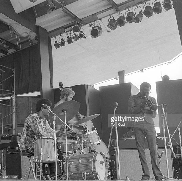 Drummer Jack Dejohnette, bassist Dave Holland and musician Miles Davis plays his trumpet at the Newport Jazz Festival on July 4, 1969 in Newport,...
