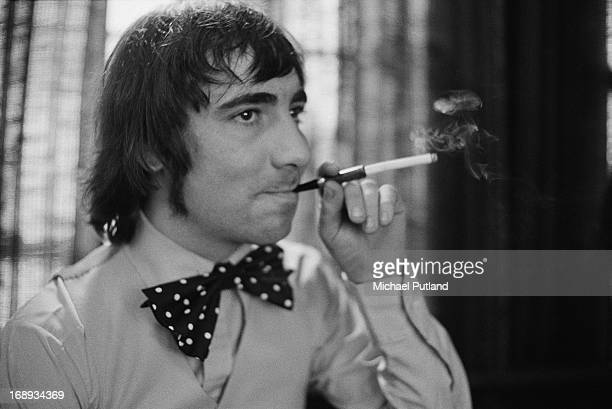 Drummer Keith Moon of English rock group The Who wearing a large bow tie and using a cigarette holder 24th April 1973