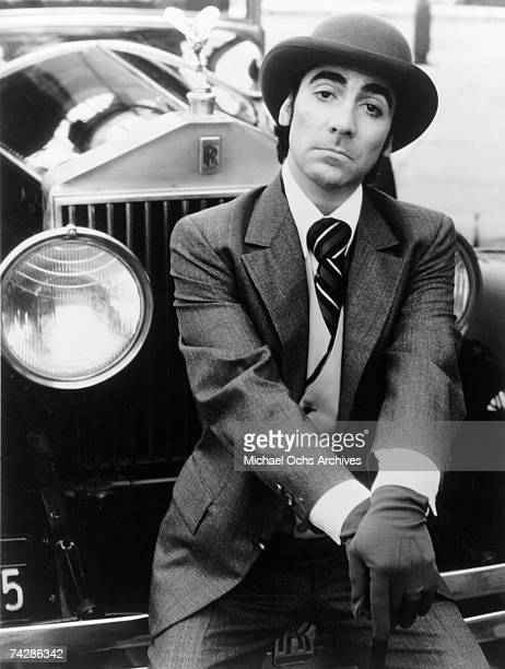 Drummer Keith Moon of the rock and roll band The Who poses for a porrait wearing a 3 piece suit and hat as he sits on the bumper of a Rolls Royce in...